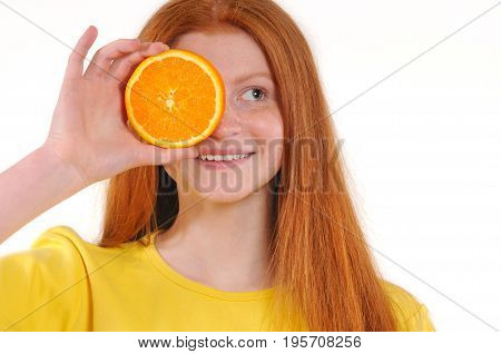 Teenage red hair girl holding piece of orange in front of her eye while standing against white background. Great food for a healthy lifestyle. Natural redhaired teenage girl