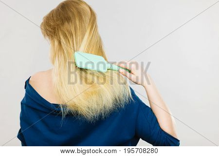 Blonde Woman Brushing Hair Back View