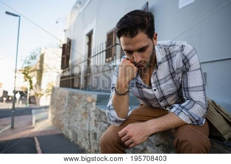 Tensed young man looking down while sitting on retaining wall