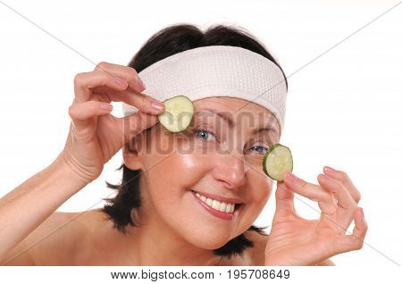 Cheerful mature woman holding pieces of cucumber in front of her eyes. Natural spa treatment. Isolated on white background
