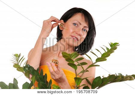 Mature woman doing rejuvenation spa procedure with aroma oil on white background. Beauty and care concept. Old skin care