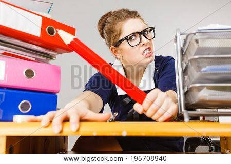 Mobbing at work bad job relations concept. Angry mad bossy businesswoman being furious sitting working at desk full off documents in binders.