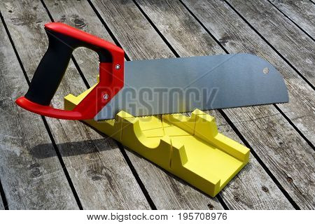 Hand Saw And A Yellow Miter Box To Make Precise Mitre Cuts In A Board.