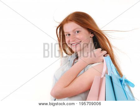 Beautiful young redhair woman with shoping bags. Isolated over white background. Studio shoot. Natural redhaired teenage girl.