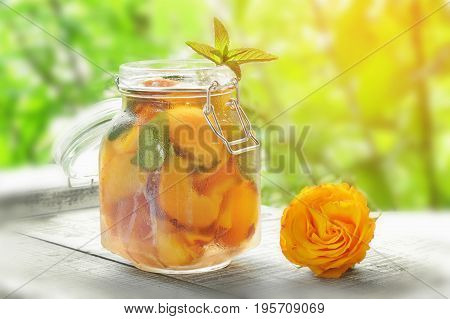 Jug with cover with water detox with pieces of peach and apricot with ice. A refreshing drink on a green background with a yellow rose. The horizontal frame. .