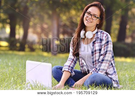 Student girl working on laptop, sitting on grass in park. Student studying outdoors. Freelance job, online shopping, distance learning concept