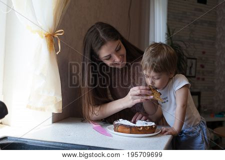 mother and son eating pie cooked in the kitchen yourself