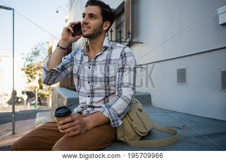 Young man talking on mobile phone while sitting on retaining wall