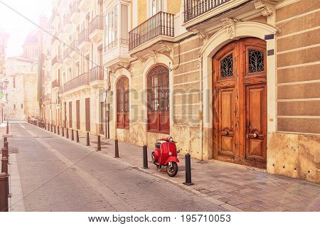 Spain. Valencia. A street in the tourist city of Valencia. Red motorcycle moped. Tourist concept. Journey. Red vintage scooter parked on a sidewalk.