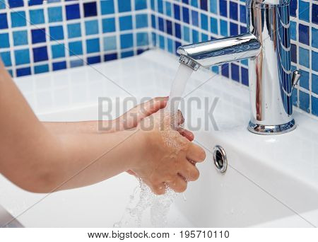 The child washes his hands in the bathroom.