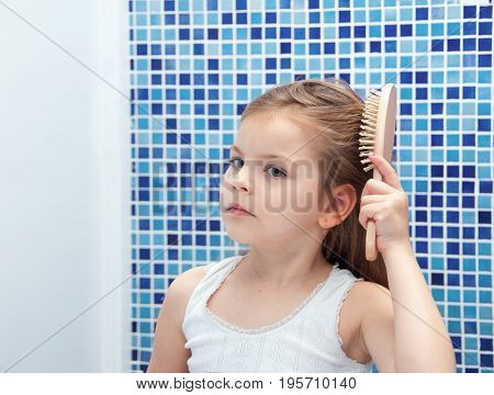 A beautiful girl is combing her hair in the bathroom.