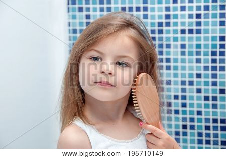 A beautiful girl is combing her hair in the bathroom. Girl got her hair tangled. The girl pouted resentful and capricious.