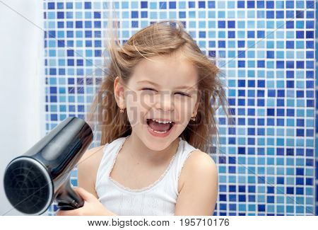 Beautiful girl in the bathroom blow dry with foams. Little girl smiling.