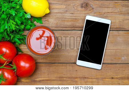 Fresh Tomato Juice, Tomatoes And Mobile On A Wooden Table Top View, Copy Space.