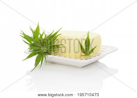 Cannabutter with marijuana leaf on saucer isolated on white background. Cannabis butter natural remedy.