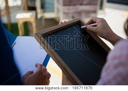 Cropped hands of woman writing menu while coworker holding file