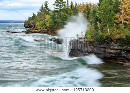 Crashing waves break agains a rocky shoreline at Pictured Rocks National Lakeshore in the Upper Penisula of Michigan