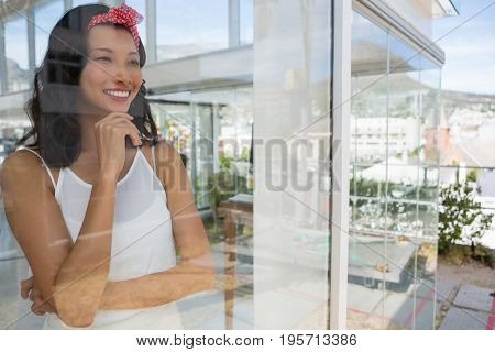 Smiling thoughtful businesswoman looking through window seen through glass