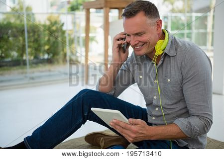 Smiling designer using tablet computer while talking on smart phone at office