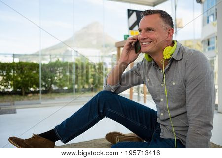 Smiling designer looking away while talking on smart phone at office