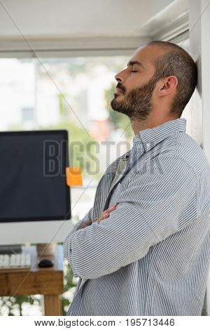 Designer with arms crossed relaxing while leaning on wall at studio