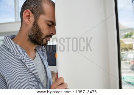 Frustrated designer leaning on wall at office
