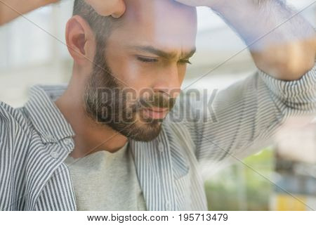 Thoughtful designer looking through window at office seen through glass