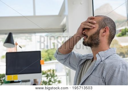 Frustrated designer leaning on glass window at office
