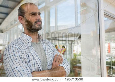 Thoughtful designer with arms crossed looking through window seen through glass