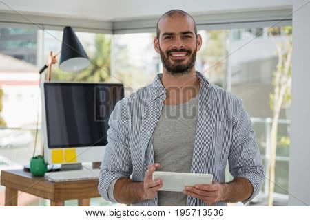 Portrait of smiling designer using digital tablet while standing in office