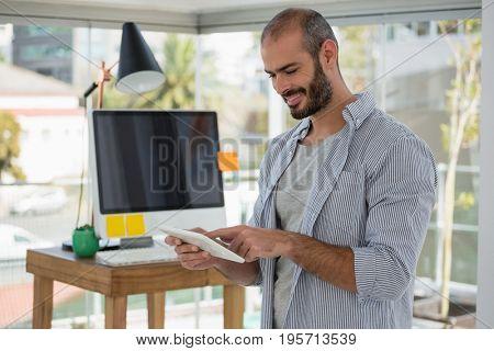 Smiling designer using digital tablet while standing in office