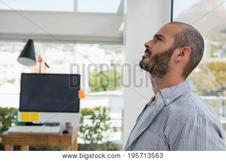 Thoughtful designer looking up while leaning on glass window at office