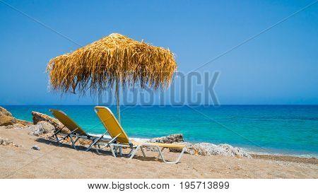 Crete Greece Agia Fothia Nomos Lassithi two beds with straw umbrella on the beach