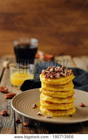 Pumpkin pancakes with pecans on a wood background