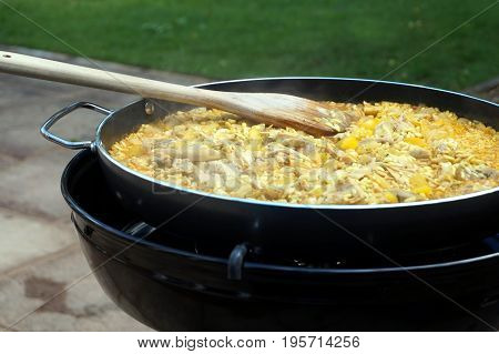 Pan Of Chicken Paella Cooking On An Outdoor Gas Cooker
