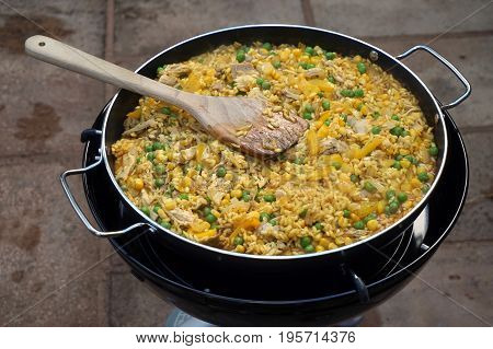 Paella With Chicken, Peas, Sweetcorn And Pepper Cooking On An Outdoor Camping Cooker