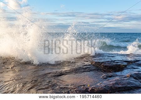 Lake Superior gale force winds drive a crashing wave over sandstone rock at Pictured Rocks National Lakeshore in Munising Michigan
