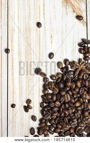 Coffee beans with anise on white wooden background.