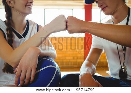 Close-up of female basketball player doing fist bump with male coach while sitting in court