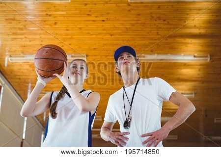 Low angle view of male coach advising female basketball player while practicing in court
