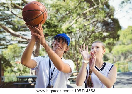 Coach training basketball player during practise in court