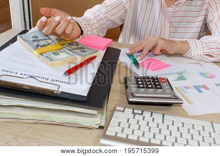 Close-up of a spreadsheet with pen and calculator. view of bookkeeper or financial inspector hands making report calculating or checking balance