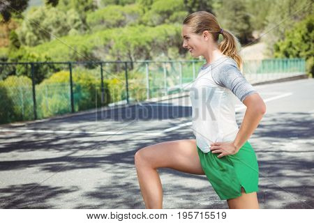 Side view of smiling woman exercising against railing on sunny day