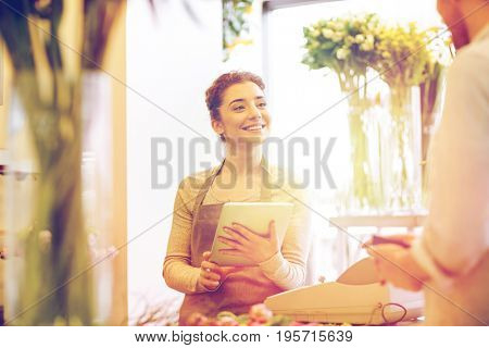 people, shopping, sale, floristry and consumerism concept - happy smiling florist woman with tablet pc computer and man with wallet at flower shop