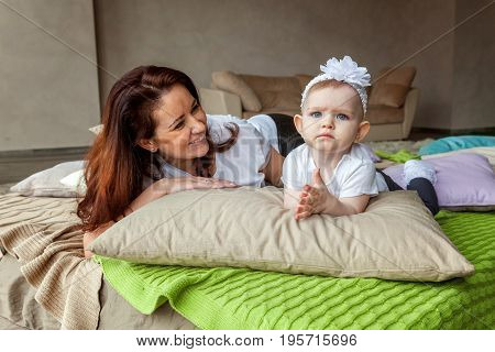 Young mother playing with her young daughter. Woman and new born girl relax in a bedroom. Mother breast feeding baby. Family at home.