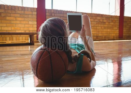 Female basketball player using tablet computer while lying on floor in court
