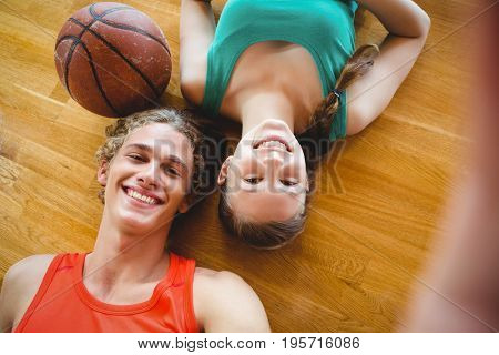 Overhead portrait of smiling friends lying on floor in basketball court