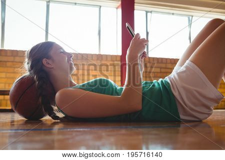 Side view of smiling woman using digital tablet while lying on floor in basketball court