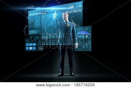 business, technology and people concept - businessman in suit touching virtual screen over black background