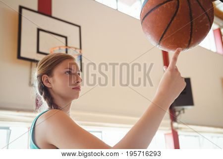 Side view of basketball player balancing ball on finger while practicing in court